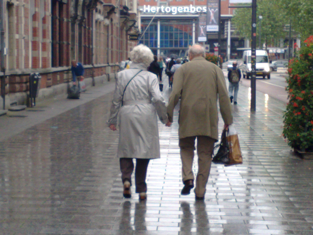 Old people holding hands and kissing